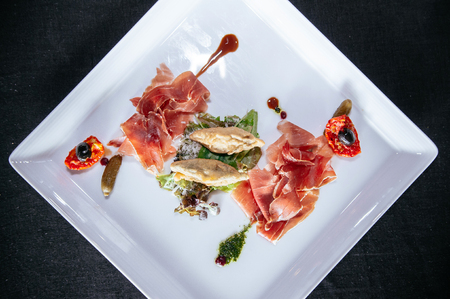 Tasty green mix salad with prosciutto ham, sundried tomato, black olive, parmesan cheese and pesto