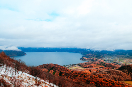 Hokkaido Usuzan mountain forest and lake Toya in urly winter with autumn foliage yellow tree, aerial view in morning