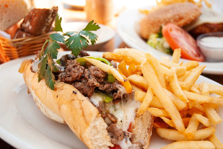 American tender beef cheese steak sub  sandwich and fries on white plate