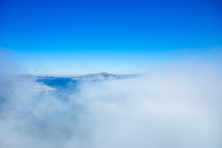 Landscape of Marin headland and San Francisco bay on foggy day with clear blue sky