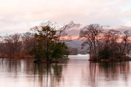 Mount Komagatake dramatic evening view from Onuma Quasi-National park lake Hokkaido in winter