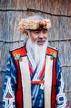NOV 20, 2013 Hokkaido, JAPAN - A man in Ainu tradition tribal costume at Shiraoi Ainu Museum. The indigenous people of northern Japan. Publikacyjne