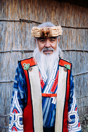 NOV 20, 2013 Hokkaido, JAPAN - A man in Ainu tradition tribal costume at Shiraoi Ainu Museum. The indigenous people of northern Japan. 報道画像
