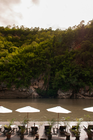 Resort style beach daybeds and white umbrellas by river Kwai, Kanchanaburi, Thailand Editorial