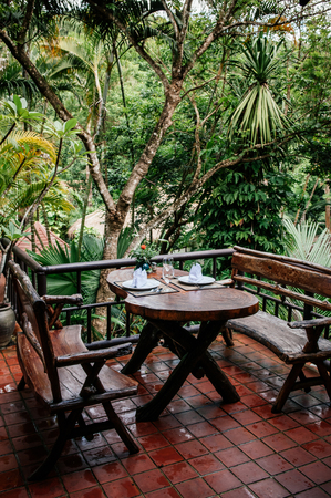 JUL 13,2013 Kanchanaburi, Thailand - Asian outdoor living area with wooden  benches and table in tropical garden 報道画像
