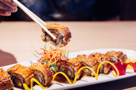 Hand Picking beautiful piece Japanese grilled Unagi Maki roll with chopstick close up shot Stock Photo