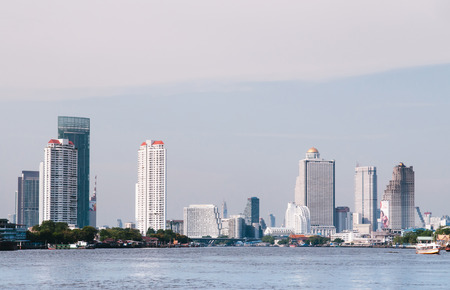 APR 20, Bangkok, Thailand - Bangkok cityscape with high ris ebuildings seen from calm Chao Praya River Stock fotó