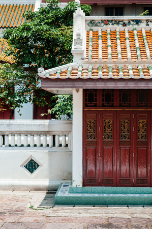 Red old carved wooden Chinese folding door of Wat Ratchaorotsaram  Bangkok, Royal temple in Thonburi district.