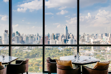 AUG 26, 2013 Bangkok, Thailand - Art deco interior dining room, vibrant desingn with glass wall Bangkok city center view, luxury diner table set and armchairs