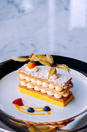 Beautiful dish of mango berries Millefeuilles French puff pastry on elegant plate on marble table