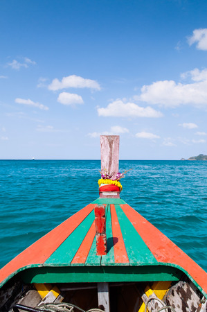 Colourful Thai fishing boat nose in Tueqouise sea of Phuket on bright summer day