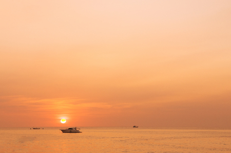 Golden sky sunset with silhouette boat in Phuket island, Thailand 写真素材