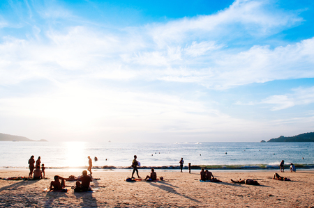 FEB 9, 2013 Phuket, THAILAND - Silhouette image of tourists take sunbathing in warm summer evening at Patong beach