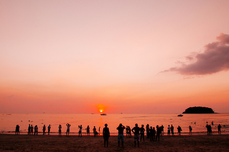 Silhouette image of tourists watching summer sunset at famous  Patong beach, Phuket 写真素材