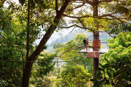 FEB 10, 2013 Phuket, THAILAND -  Tourists on zip line elevated platform over tropical forest canopy, famous adventure activity beside beach and sea