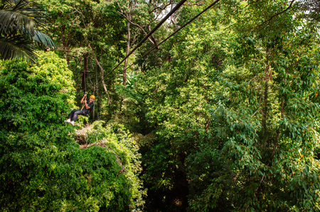 FEB 10, 2013 Phuket, THAILAND - Male tourist on zip line over lush tropical forest canopy, famous adventure activity beside beach and sea