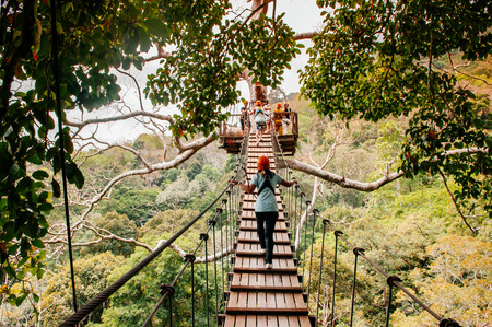 FEB 10, 2013 Phuket, THAILAND -  Tourists on zip line elevated  wooden bridge over tropical forest canopy, famous adventure activity beside beach and sea