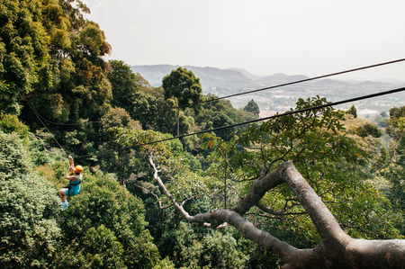 FEB 10, 2013 Phuket, THAILAND -  Male tourist on zip line over lush tropical forest canopy, famous adventure activity beside beach and sea 写真素材