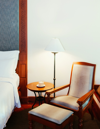 FEB 8, 2013 Phuket, Thailand - Old classic teak wood table, chair and lamp, bedroom with white wall - Asian vintage home Interior warm atmosphere