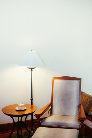 FEB 8, 2013 Phuket, Thailand - Old classic teak wood table, chair and lamp with white wall - Asian vintage home Interior warm atmosphere 写真素材