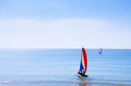 Phuket vibrant turqoise blue sea at Mai Khao beach with sailboat, view from distance