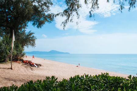 Trop[ical Phuket vibrant turqoise blue sea at Mai Khao beach with tourists, tree bush and pine tree 写真素材