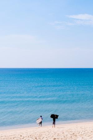 Phuket turqoise blue sea water at Mai Khao beach with tourists take holding durf board run along the beach, Thailand