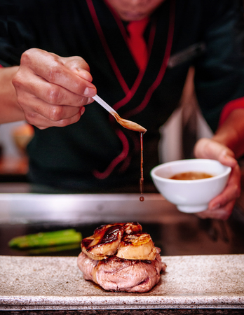 Dripping gravy sauce on Fillet mignon steak with Foie Gras and spring asparagus Japanese Teppanyaki dining style 写真素材