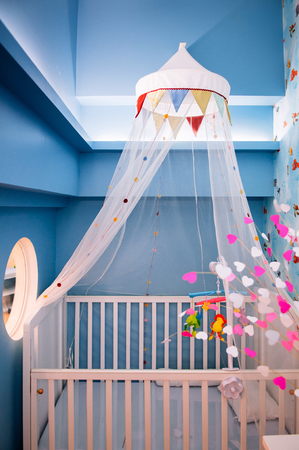 FEB 8, 2013 Phuket, Thailand - Cute stylish designed interior of baby room with wooden crib, mosquito net hanging from ceiling and artificial colourful flowers