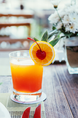 A glass of fresh squeeze orange juice with orange slice and pickled cherry on breakfast table 写真素材