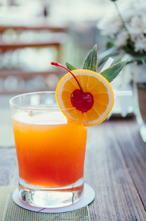 A glass of fresh squeeze orange juice with orange slice and pickled cherry