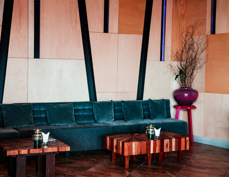 FEB 8, 2013 Phuket, Thailand - High ceiling modern living room dark blue couch, red stool, ceramic vase, wooden coffee table, warm tone marble wall, stylish hotel or contemporary resort decoration