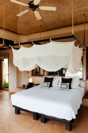 FEB 6, 2013 Phuket, Thailand - Tropical Resort bedroom with wooden bed, stylish mosquito net and pillows, warm simple asian interior atmosphere Publikacyjne