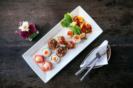 Aperitivo de varios canapés de estilo asiático: salmón ahumado, sushi maki, larb, tartar de atún, rollito de primavera y camarones a la parrilla Foto de archivo