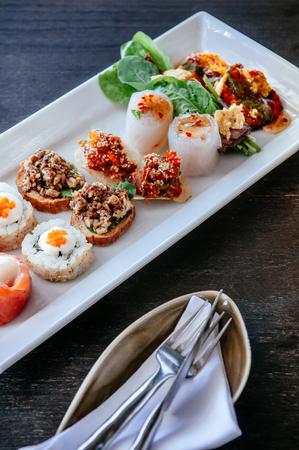 Aperitivo de varios canapés de estilo asiático: salmón ahumado, sushi maki, larb, tartar de atún, rollito de primavera y camarones a la parrilla