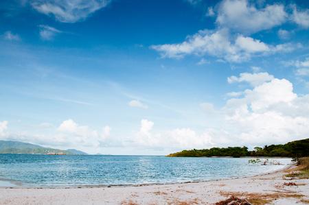 Peaceful white sand beach and blue sky of Koh Mud Sum small island near Koh Samui isalnd, Thailand.