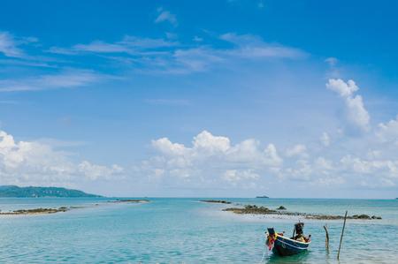 Thai Longtail Fishing Boat at Koh Tean rocky beach near Samui island in summer day with blue sky, Thailand tropical island