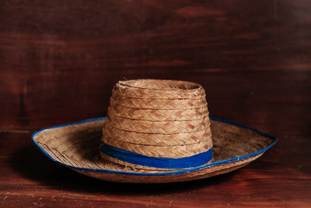 Vintage retro asian style straw hat with blue ribbon on wood background, rustic farmer hat