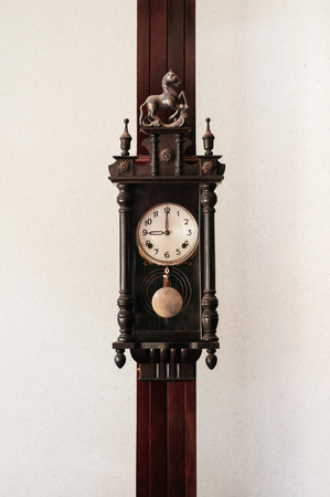 Old vintage carved dark wood grandfather wall clock hanging on wood pillar white wall background 写真素材