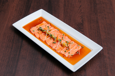 Fresh salmon tataki with hamemade ponzu sauce and Kaiware sprouts in white plate on wood table Stock Photo