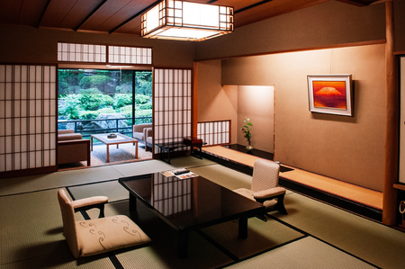 MAY 25, 2013 Gifu, JAPAN - Vintage Traditional Japanese living room with sliding doors, Tatami mat floor black wood table and retro design seats. Warm light and atmosphere from ceiling lamp