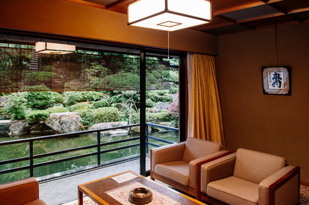 MAY 25, 2013 Gifu, JAPAN - Vintage Japanese hotel living room with sliding doors, wood table and retro design armchairs. Warm light and atmosphere with garden view Editorial