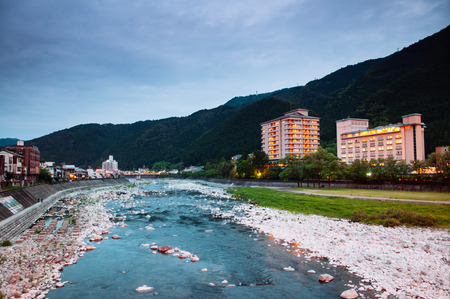 Natural stream and green mountain valley of Gero onsen resort town at sunset time in Gifu prefecture, Japan