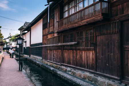 MAY 26, 2013 Gifu, JAPAN - Old traditional wooden houses and Japanese tourist on street and small natural stream of Hida Furukawa town old historic town. Редакционное