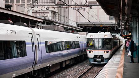 MAY 29, 2013 Nagano, Japan - Azusa express and Shinano line trains arriving at platform of  JR Chuo Main line at Matsumoto station with Japanese passengers waiting behind yellow line Редакционное