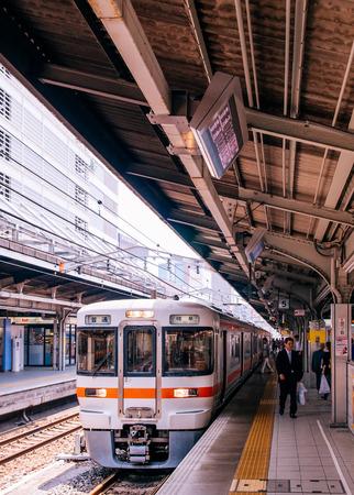 MAY 30, 2013 Nagoya, Japan - Gifu local train line stop at platform of JR Chuo Main line at Nagoya station with Japanese passengers walking behind yellow line Редакционное