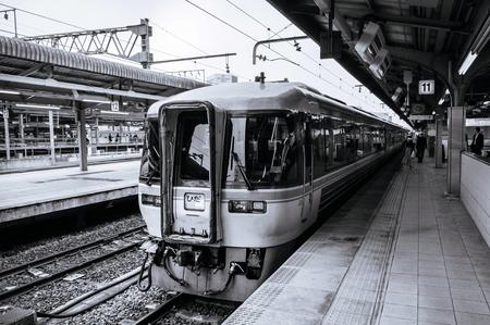 MAY 30, 2013 Nagoya, Japan - Hida train line stop at platform of JR Chuo Main line at Nagoya station with Japanese passengers walking behind yellow line