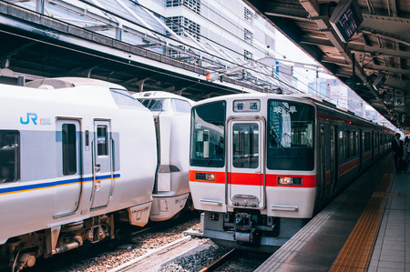 MAY 30, 2013 Nagoya, Japan - Gifu train line stop at platform of JR Chuo Main line at Nagoya station with Japanese passengers walking behind yellow line