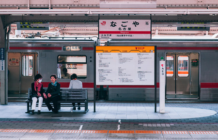 MAY 30, 2013 Nagoya, Japan - Passengers waiting at platform of JR Nagoya station with station sign and local train in background - vintage film style image
