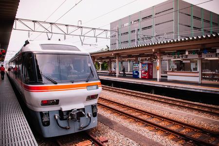 MAY 30, 2013 Nagoya, Japan - Hida train line stop at platform of JR Takayama station with Japanese passengers walking behind yellow line Редакционное